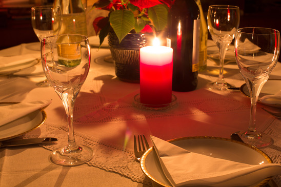 Dinner table in candle light with flowers, glasses and plates