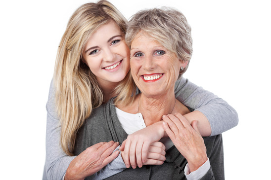 Happy Teenage Girl Embracing Grandmother From Behind