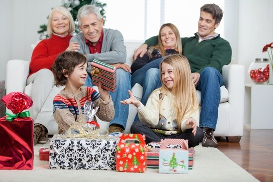 Family With Christmas Presents At Home